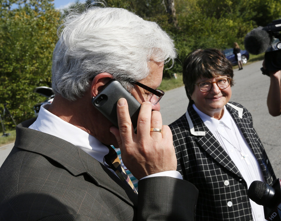Photo - Don Knight, attorney for Richard Glossip, talks on the phone to Glossip as Sister Helen Prejean looks on after the scheduled execution of Richard Eugene Glossip was stayed at the Oklahoma State Penitentiary in McAlester, Okla., Wednesday, Sept. 30, 2015. Gov. Fallin stayed the execution for 37 days. Photo by Nate Billings, The Oklahoman