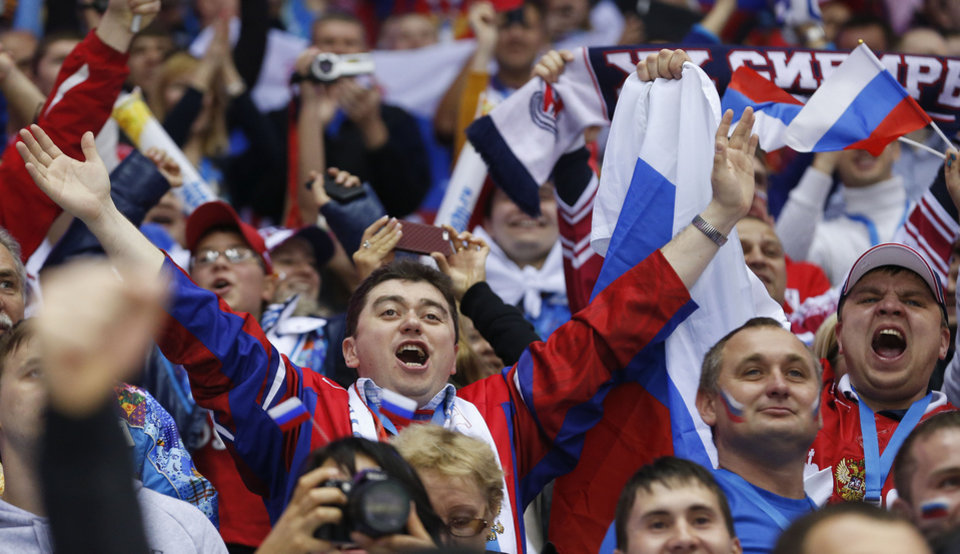 Photo - Hockey fans cheer for Russia in the first period of a men's ice hockey game against Slovenia at the 2014 Winter Olympics, Thursday, Feb. 13, 2014, in Sochi, Russia. (AP Photo/Julio Cortez)