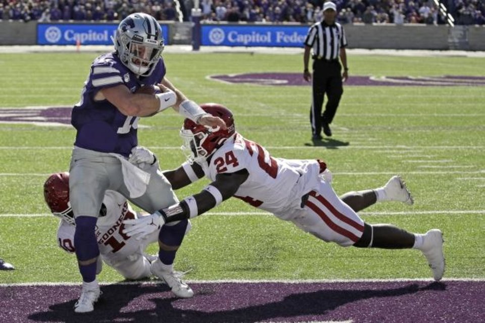 Photo -  Kansas State quarterback Skylar Thompson (10) runs into the end zone for a touchdown Saturday through Oklahoma's Brian Asamoah (24) and Pat Fields (10). [AP Photo/Charlie Riedel]