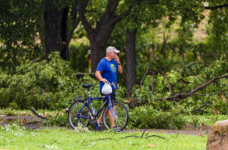 Photo - A cyclist pushes his bike through the tree limbs that cover the Del City Trail after storms caused damage in Del City, Okla. on Tuesday, Aug. 27, 2019.   [Chris Landsberger/The Oklahoman]