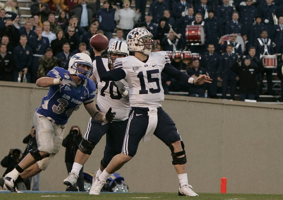 Photo - BYU quarterback Max Hall (15) is pursued by Air Force safety Chris Thomas (34) as BYU offensive lineman Matt Reynolds (70) tries to protect his quarterback in the fourth quarter of BYU's 38-24 win in an NCAA college football game at Air Force Academy, Colo., Saturday, Nov. 15, 2008. Hall threw for 354 yards and two touchdowns in the victory. (AP Photo/Justin Edmonds) ORG XMIT: COJE112