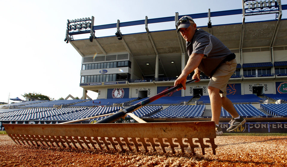 Photo - In this May 22, 2014 photo, Nick McKenna, from Texas A&M, rakes in calcined clay along the baseline at the Southeastern Conference NCAA college baseball tournament in Hoover, Ala. The work began three days before the six-day, 17-game tournament. (AP Photo/Butch Dill)