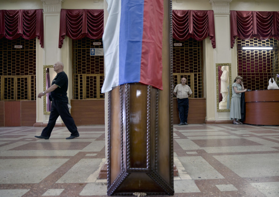 Photo - A coffin cover is draped with the Russian flag during a funeral, attended by thousands, for five pro-Russian activists, Saturday, May 24, 2014, in the town of Stakhanov, eastern Ukraine. Five insurgents killed in a battle with Ukrainian forces near the city of Luhansk were buried on Saturday. The clash is one of several firefights between the two sides that have left at least 20 dead and some 300 injured, according to the Ukrainian Defense Ministry, days ahead of the country's presidential elections. (AP Photo/Vadim Ghirda)