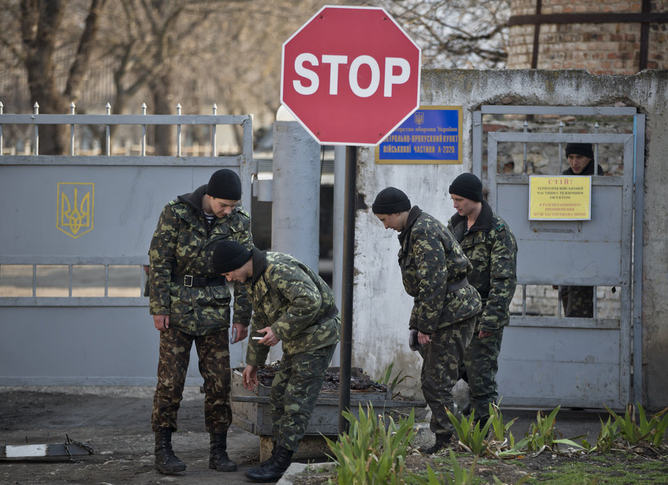 Photo - Ukrainian soldiers carry garbage outside the Ukrainian infantry base in Perevalne, Ukraine, Wednesday, March 12, 2014. The Group of 7 world leaders said in a statement released from the White House on Wednesday that they won't recognize results of a referendum for the Crimea region to split from Ukraine and join Russia.(AP Photo/Vadim Ghirda)