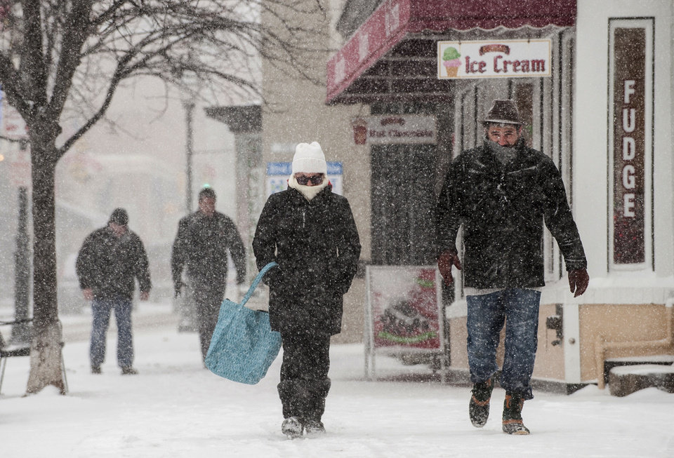 Photo - Caroline and Paul Banker, of Annapolis, Md., brave the snow as they walk down the city's Main Street towards the city dock during Tuesday's, Jan. 21, 2014, snowstorm. (AP Photo/Capital Gazette,  Matthew Cole)