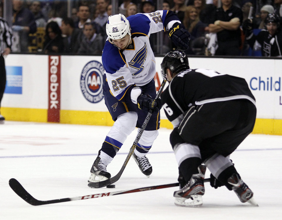 Photo - St. Louis Blues right wing Chris Stewart (25) controls the puck to get around Los Angeles Kings defenseman Jake Muzzin (6) during the first period of an NHL hockey game Tuesday, March 5, 2013, in Los Angeles.  (AP Photo/Alex Gallardo)