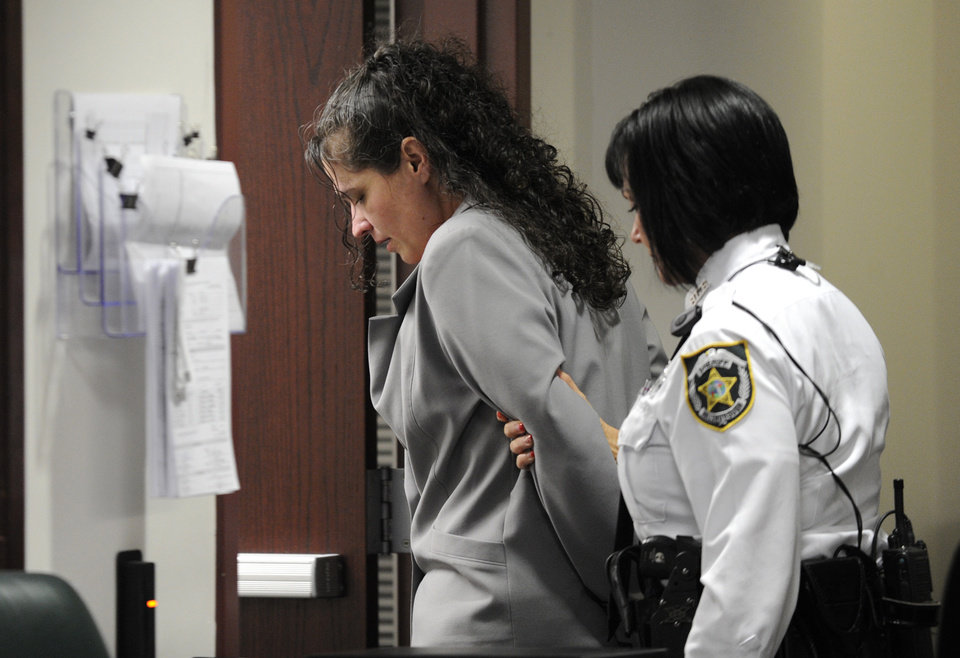 """Photo - Dee Dee Moore is led from a Hillsborough County courtroom after being found guilty of first-degree murder in the death of lottery winner Abraham Shakespeare Monday, Dec. 10, 2012 in Tampa, Fla. Moore was convicted Monday of first-degree murder in the slaying of a lottery winner in central Florida and sentenced to mandatory life without parole by a judge who called her """"cold, calculating and cruel.""""(AP Photo/The Tampa Tribune, Chris Urso, Pool)"""