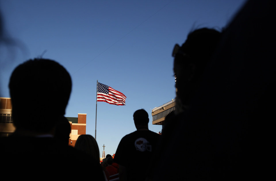 Photo - People stand during the national anthem  before a college football game between the Oklahoma State University Cowboys (OSU) and the University of Arizona Wildcats at Boone Pickens Stadium in Stillwater, Okla., Thursday, Sept. 8, 2011. Photo by Sarah Phipps, The Oklahoman  ORG XMIT: KOD