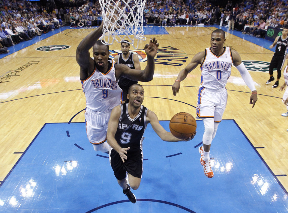 Photo - San Antonio Spurs guard Tony Parker (9) goes up for a shot in front of Oklahoma City Thunder forward Serge Ibaka (9) and guard Russell Westbrook (0) during the second quarter of an NBA basketball game in Oklahoma City, Thursday, April 3, 2014. Oklahoma City won 106-94. (AP Photo/Sue Ogrocki)