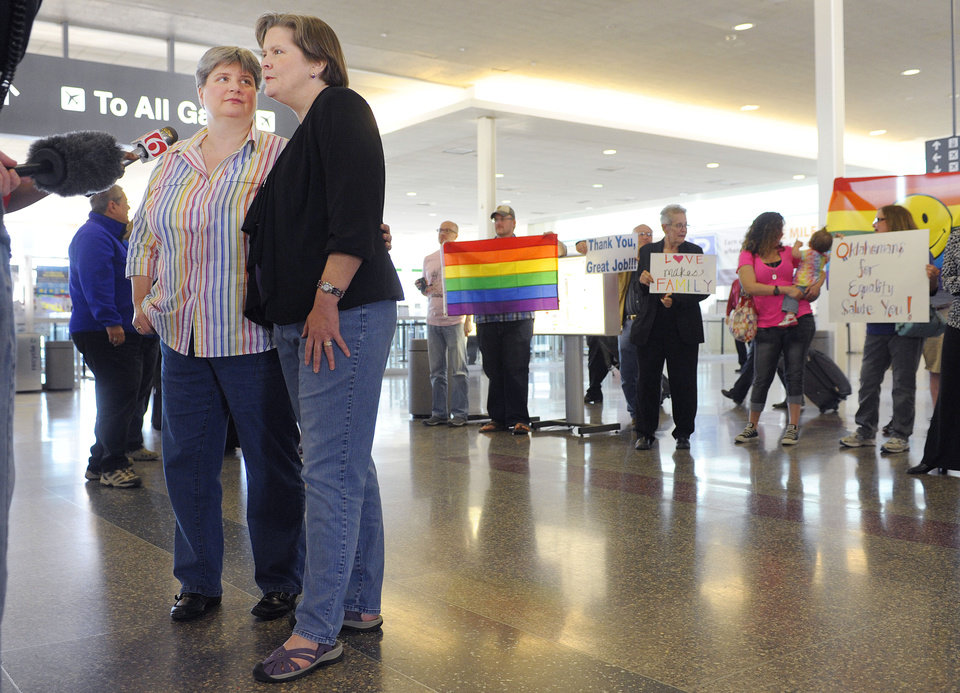 Photo -                    Sharon Baldwin, left, and her partner Mary Bishop speak with members of the media before boarding a plane to Denver on Wednesday at Tulsa International Airport. Baldwin and Bishop plan to attend hearings at the 10th U.S. Circuit Court of Appeals in Denver on their lawsuit challenging Oklahoma's ban on gay marriage.                     ASSOCIATED PRESS
