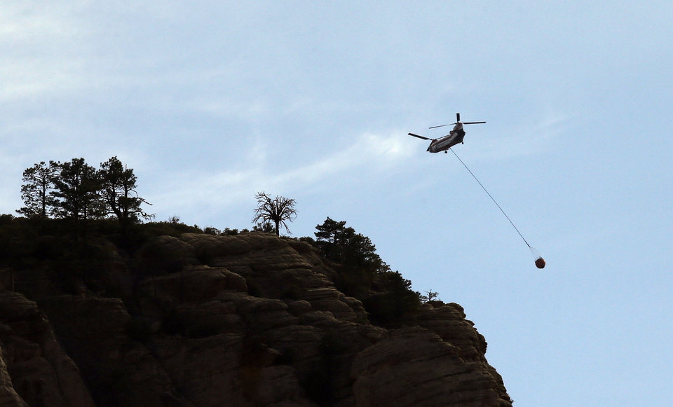 Photo - A helicopter fighting the Slide Fire leaves the scene for a refill as the fire burns up Oak Creek Canyon on Thursday, May 22, 2014, in Sedona, Ariz.  The fire has burned approximately 4,800 acres. (AP Photo/Ross D. Franklin)
