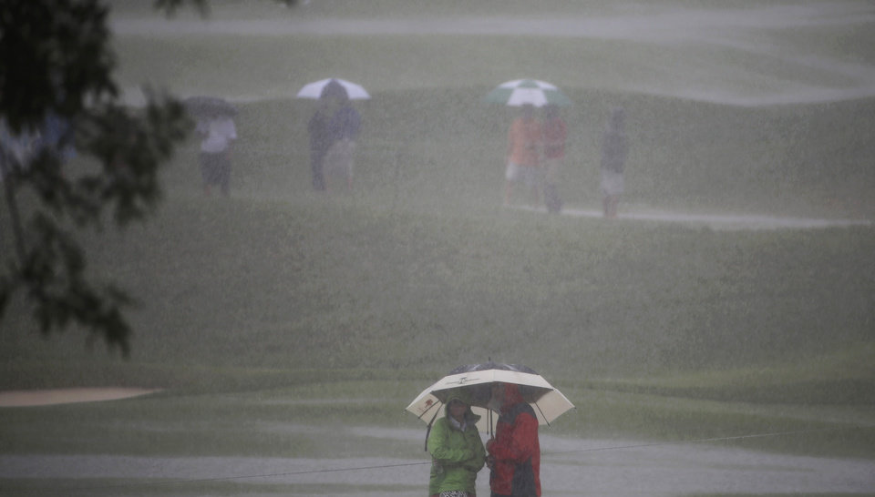 Photo - Golf fans wait out a rain delay on the first hole during the final round of the PGA Championship golf tournament at Valhalla Golf Club on Sunday, Aug. 10, 2014, in Louisville, Ky. (AP Photo/David J. Phillip)