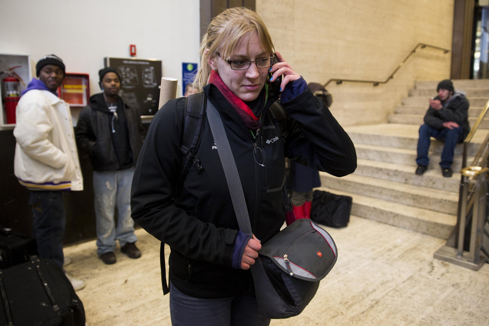 Photo - Sarah Magnuson, of Columbus, Ohio makes phone calls after arriving at Union Station after her Amtrak train from Los Angeles became stuck in snow drifts on Tuesday, Jan. 7, 2014, in Chicago. The severe weather forced hundreds of Amtrak passengers to spent the night onboard three trains stranded due to the snow in northern Illinois. (AP Photo/Andrew A. Nelles)