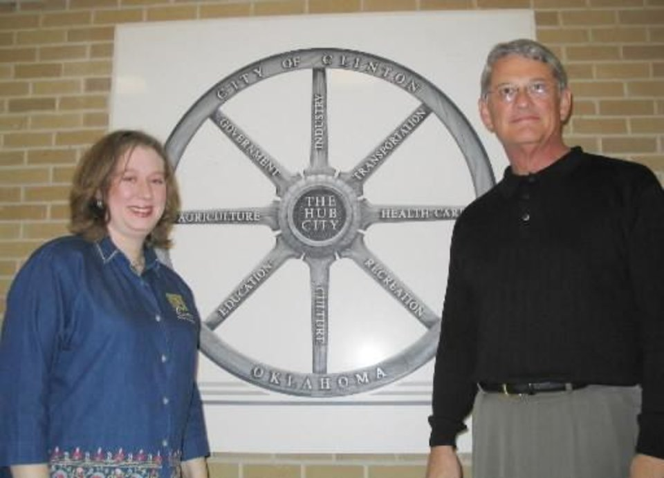 Photo - 2003 file photo - Clinton chamber president Nicole Boyles and new city manager  Grayson  Bottom pose in front of the city's current logo at city hall. By Ron Jackson. Nov. 11.