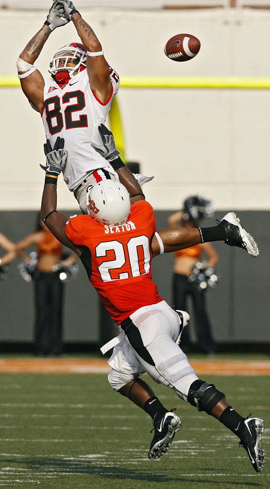Photo - Oklahoma State's Andre Sexton (20) breaks up a pass for Georgia's Michael Moore (82)  during the college football game between OSU and the University of Georgia at Boone Pickens Stadium on the campus of Oklahoma State University in Stillwater Saturday, Sept. 5, 2009. Photo by Chris Landsberger, The Oklahoman. ORG XMIT: KOD