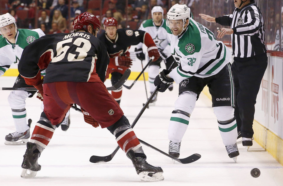 Photo - Dallas Stars' Vernon Fiddler (38) loses control of the puck in front of Phoenix Coyotes' Derek Morris (53) during the first period of an NHL hockey game, Tuesday, Feb. 4, 2014, in Glendale, Ariz. (AP Photo/Ross D. Franklin)