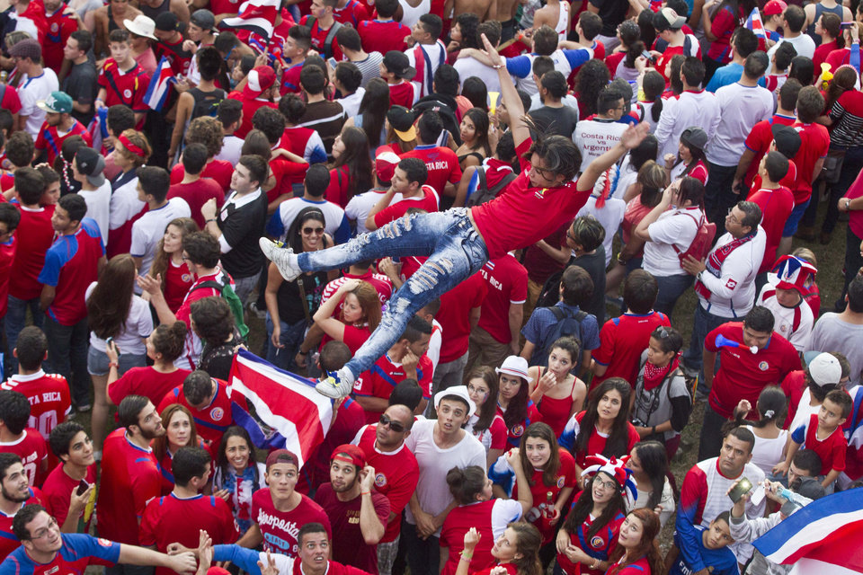 Photo - Costa Rica soccer fans throw a woman in the air as they celebrate their team's victory over Greece at a Brazil World Cup round of 16 game in San Jose, Costa Rica, Sunday, June 29, 2014. Costa Rica won a penalty shootout 5-3 after the match ended 1-1 following extra time. (AP Photo/Esteban Felix)