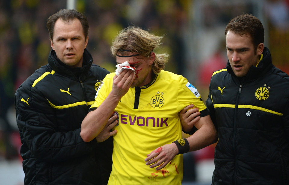 Dortmund's Marcel Schmelzer, center, is helped to leave the pitch after an injury during the German Bundesliga soccer match between VfB Stuttgart and Borussia Dortmund, in Stuttgart, southern Germany Saturday March 30, 2013. ( (AP Photo/dpa, Marijan Murat)