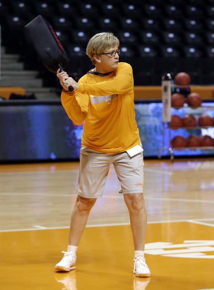 Photo - Tennessee head coach Holly Warlick holds a blocking pad as she waits for the next player to drive to the basket during practice for the NCAA women's college basketball tournament Friday, March 21, 2014, in Knoxville, Tenn. Tennessee will face Northwestern State in a first-round playoff game Saturday. (AP Photo/Mark Humphrey)