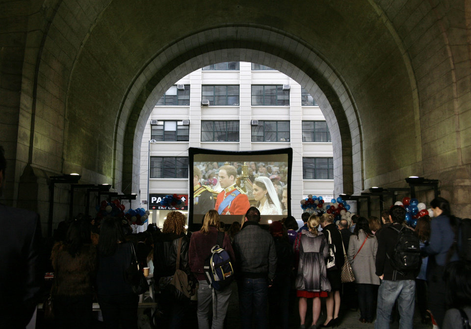 Photo - A crowd watches the wedding ceremony of Britain's Prince William and Kate Middleton on a video screen under the Manhattan Bridge in the borough of Brooklyn in New York on April 29, 2011. Some 2 billion people across the globe were believed to have tuned in as the future king and queen of England started their lives as husband and wife with the two simple words