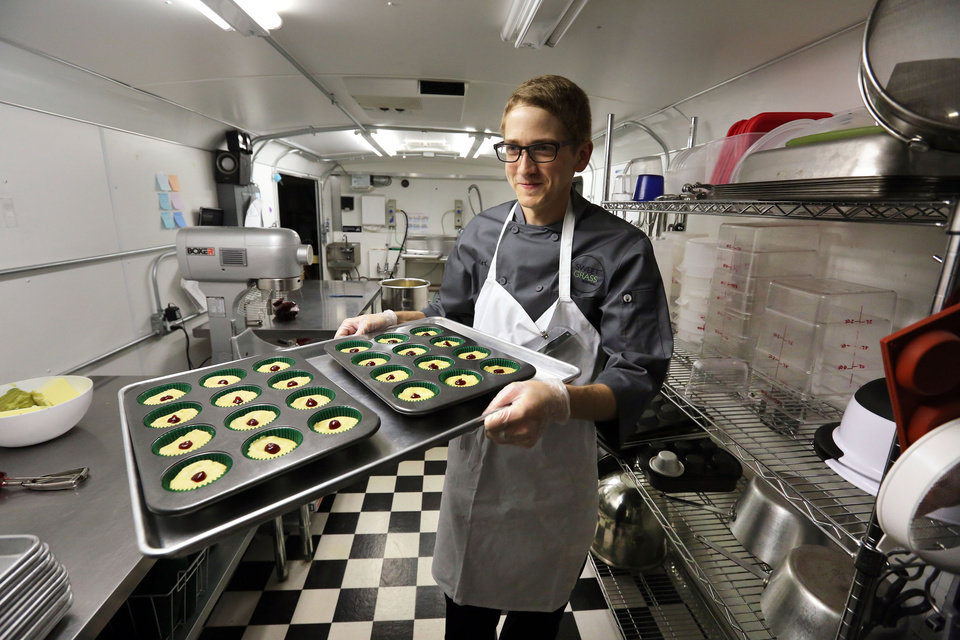 Photo - In this June 19, 2014 photo, chef Alex Tretter carries a tray of  cannabis-infused peanut butter and jelly cups to the oven for baking, at Sweet Grass Kitchen, a well-established gourmet marijuana edibles bakery which sells its confections to retail outlets, in Denver. Sweet Grass Kitchen, like other cannabis food producers in the state, is held to rigorous health inspection standards, and has received praise from inspectors, according to owner Julie Berliner. (AP Photo/Brennan Linsley)