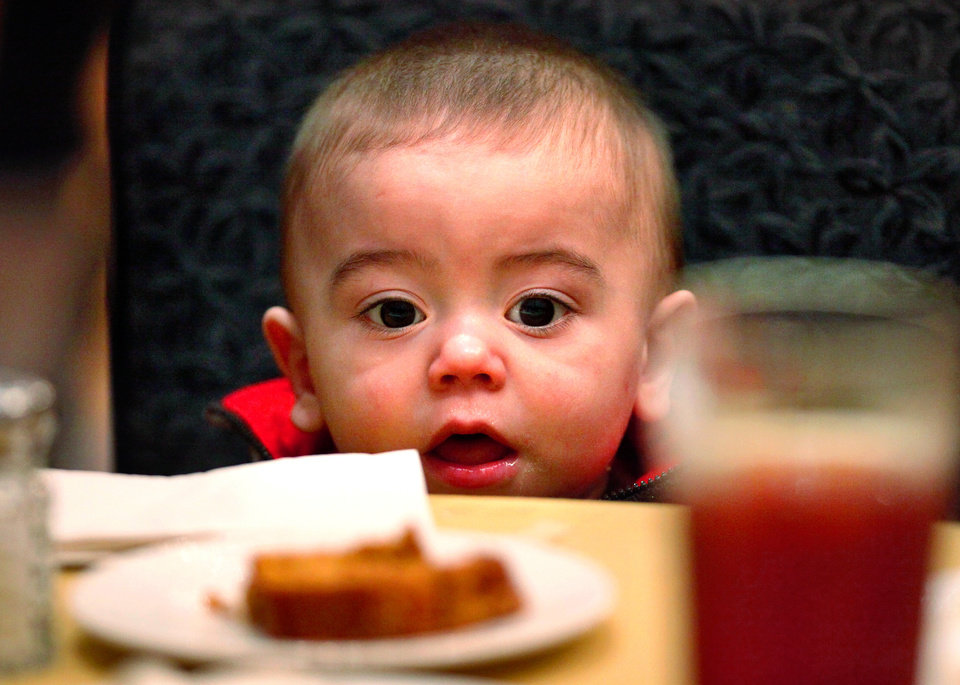 Photo - Jayden Romero, 14 months, stares at a dessert on the table in front of him  at the 30th Edmond Community Thanksgiving Dinner in the George Nigh Student Center on the campus of University of Central Oklahoma, Thursday,  Nov. 24, 2011.  Romero attended the meal with his mother, Sarah, of Edmond, and grandmother. Photo by Jim Beckel, The Oklahoman