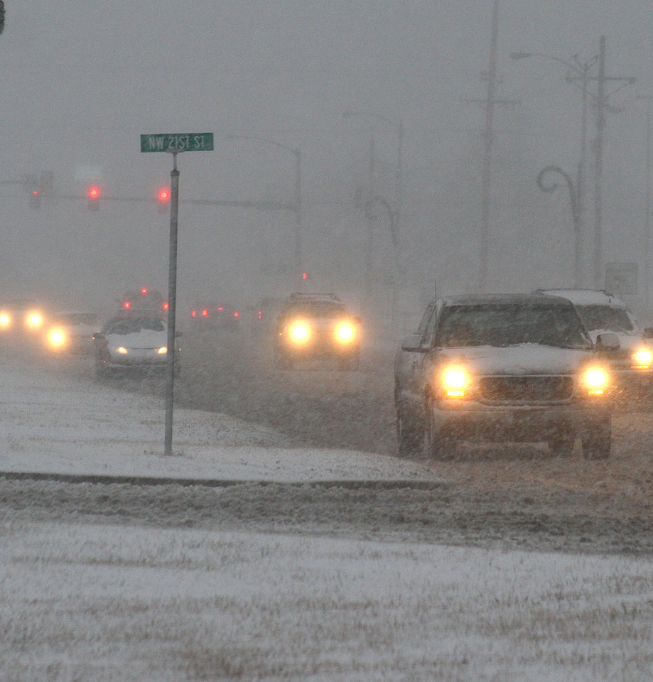 Traffic makes its way down U.S. Highway 64 in Guymon, Okla. on Dec. 19, 2011 during a heavy snow storm. A Blizzard Warning has been posted for the region with up to a foot of snow expected. (AP Photo/She Guymon Daily Herald, Shawn Yorks).