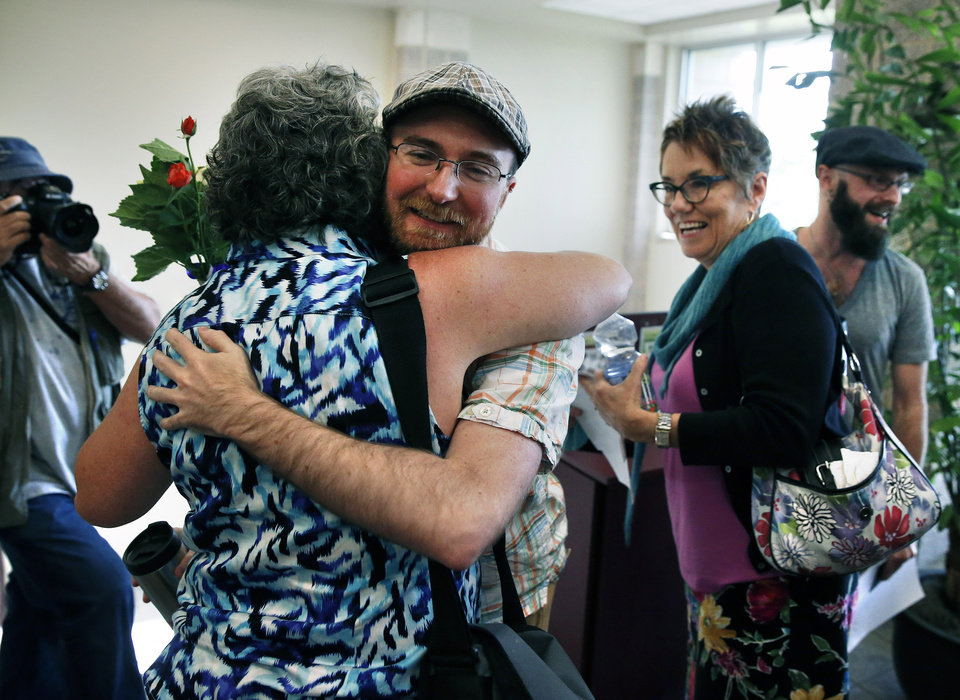 Photo - Bylo Farmer, left, is hugged and congratulated by Josh Hufford as their same-sex spouses Levi Healy, far right, and Angie Holley smile, shortly after all four received new marriage licenses, at the offices of the Boulder County Clerk and Recorder, in Boulder, Colo., Thursday, June 26, 2014. Boulder County Clerk Hillary Hall began issuing licenses a day earlier following a federal appeals court ruling that Utah's same-sex marriage ban is unconstitutional. More couples showed up in Boulder on Thursday to get licenses. (AP Photo/Brennan Linsley)