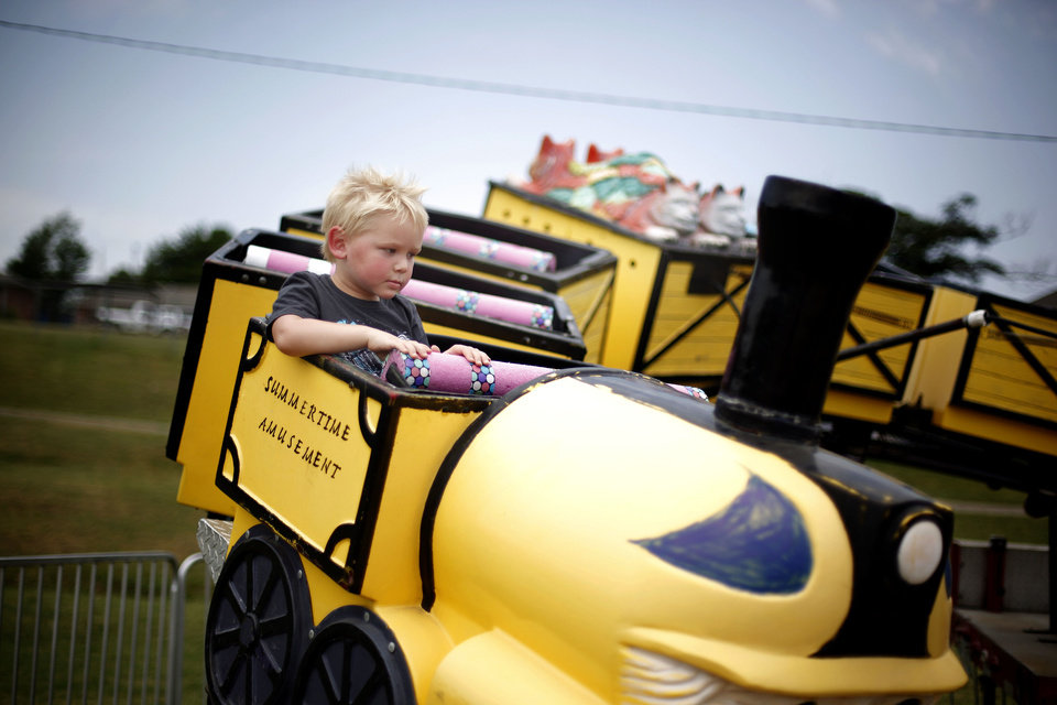 Brayln Rowley, 3, rides a train Saturday during the Blackberry festival in McLoud. Photos by Sarah Phipps, The Oklahoman