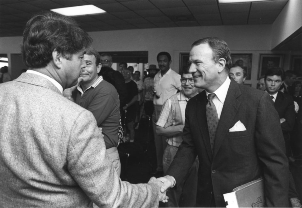 Photo - Barry Switzer greets Art Elbert, Oklahoma University vice president of administrative affairs, before announcing his resignation on June 19, 1989. PHOTO BY STEVE SISNEY, The Oklahoman Archives