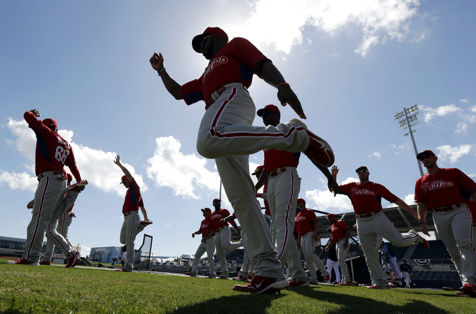 Photo - Philadelphia Phillies left fielder Zach Collier, center, warms up on the field before an exhibition baseball game against the Tampa Bay Rays, Monday, March 3, 2014, in Port Charlotte, Fla. (AP Photo/Steven Senne)