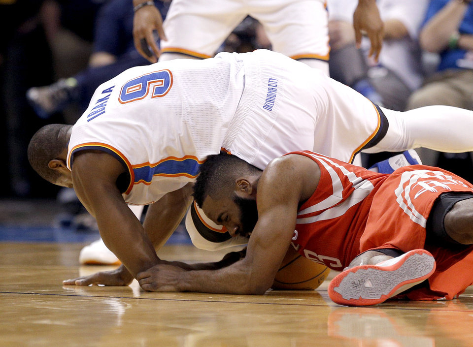 Photo - Oklahoma City's Serge Ibaka (9) tries to get a loose ball from Houston's James Harden (13) during the NBA game between the Oklahoma City Thunder and Houston Rockets at the  Chesapeake Energy Arena  in Oklahoma City, Okla., Tuesday, March 11, 2014. Photo by Sarah Phipps, The Oklahoman