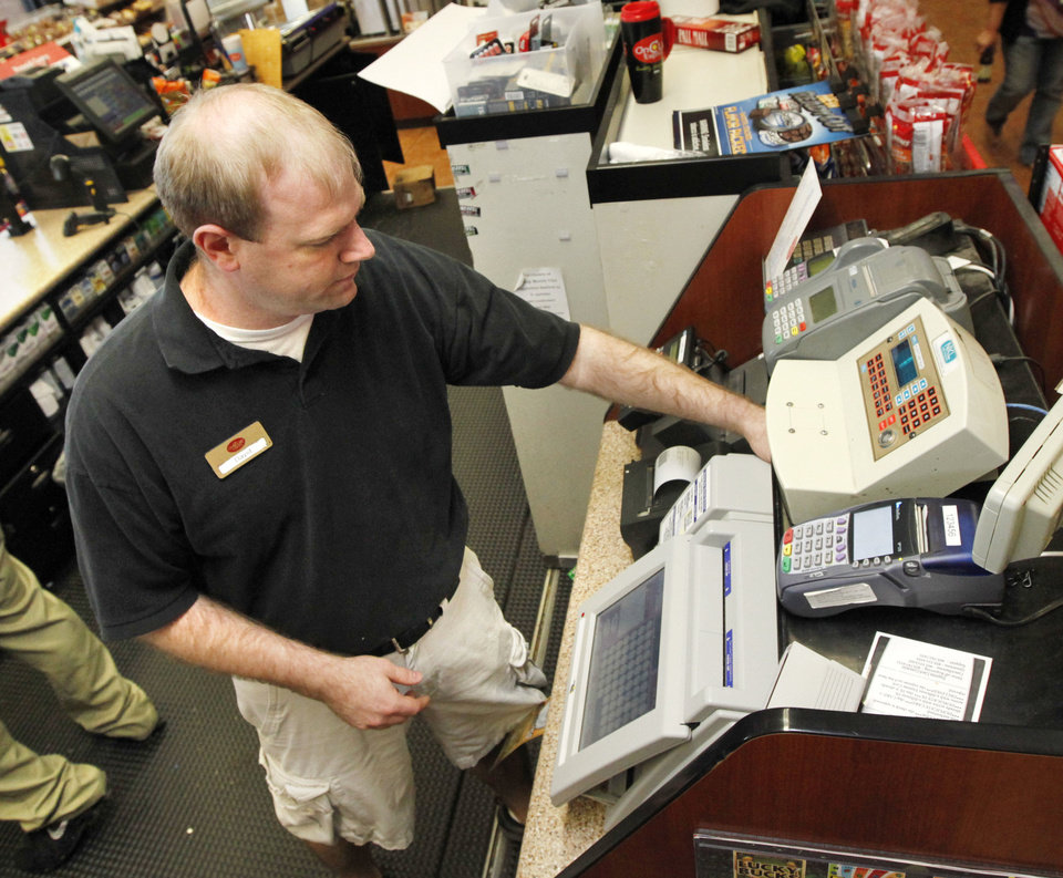 Photo - Store manager David Schwarz prints out lottery tickets Friday at the OnCue store at N 23 and Santa Fe Avenue in Oklahoma City. Photo By Paul Hellstern, The Oklahoman  PAUL HELLSTERN - Oklahoman