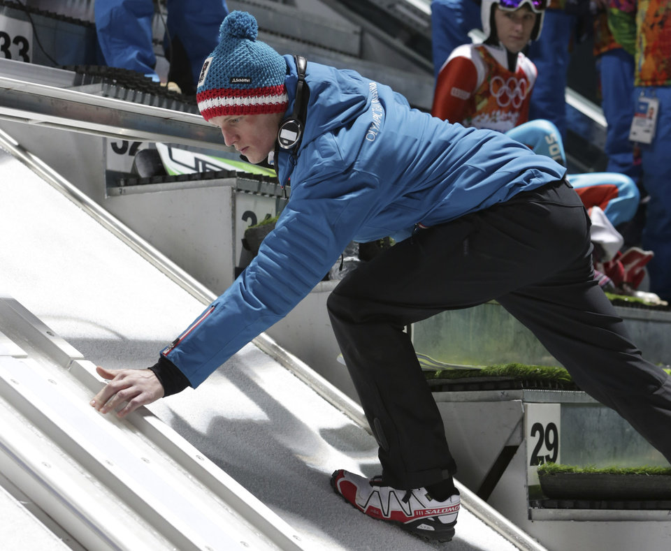 Photo - Austria's Thomas  Morgenstern checks the track before his first training attempt in the men's ski jumping from the normal hill the 2014 Winter Olympics, Thursday, Feb. 6, 2014, in Krasnaya Polyana, Russia. (AP Photo/Matthias Schrader)