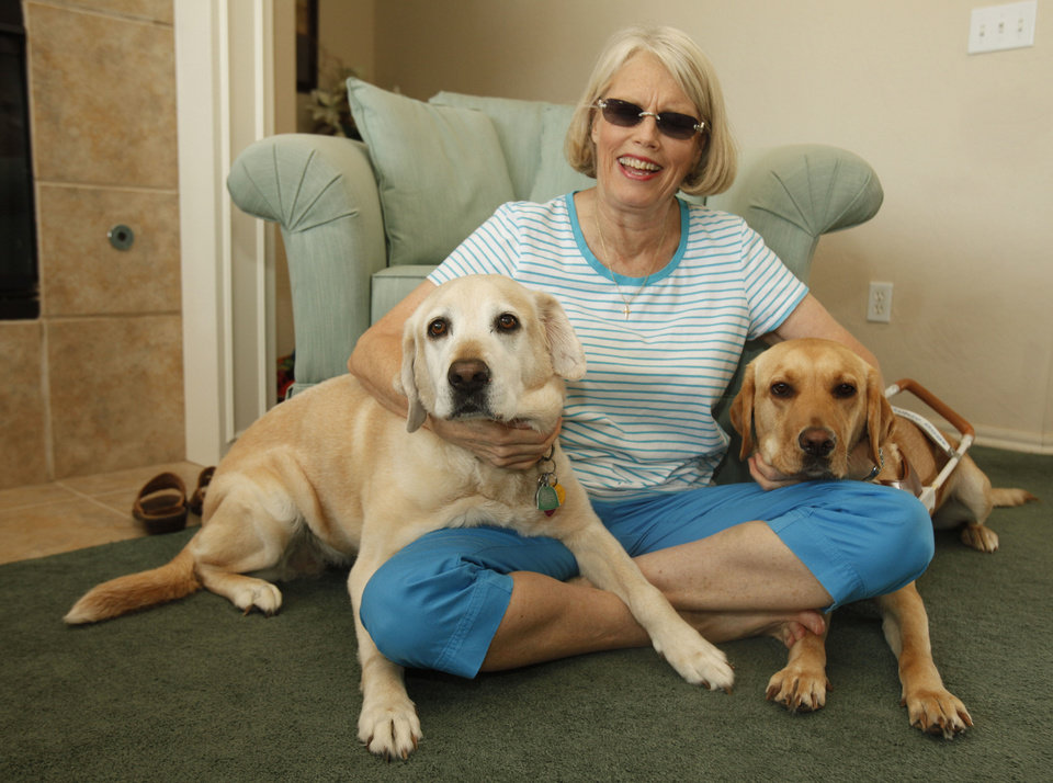 Kathleen Kennedy sits with her original guide dog, Pasha, left, and new guide dog Jamie at her home in Edmond. Photo by Paul Hellstern, The Oklahoman