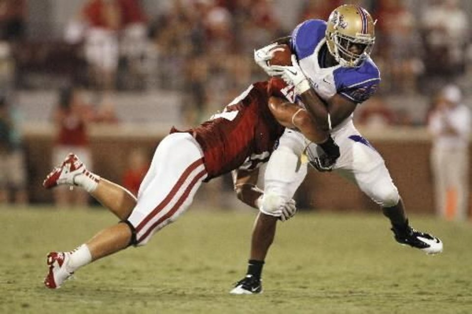 Photo - Oklahoma's Tom Wort (12) brings down Tulsa's Trey Watts (22) after a pass during the second half of the college football game between the University of Oklahoma Sooners ( OU) and the Tulsa University Hurricanes (TU) at the Gaylord Family-Memorial Stadium on Saturday, Sept. 3, 2011, in Norman, Okla. Photo by Steve Sisney, The Oklahoman ORG XMIT: KOD