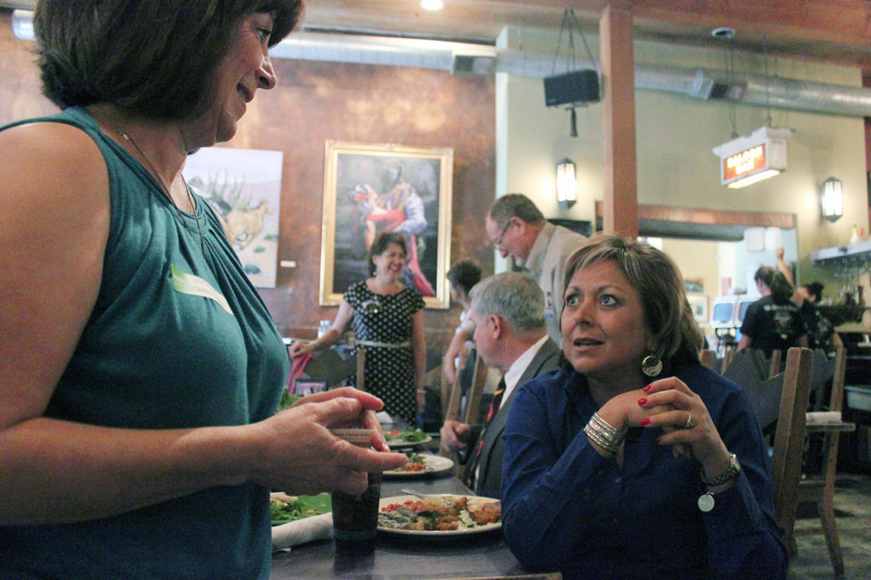 Photo - New Mexico Gov. Susana Martinez, right, takes a break from lunch to talk about green chile during a visit to The Range restaurant in Bernalillo, N.M., on Tuesday, Aug. 19, 2014. The restaurant is the first to sign up to participate in a new certification program unveiled Tuesday to protect the integrity and reputation of New Mexico-grown chile, a signature crop that infuses about $400 million into the state's economy each year. (AP Photo/Susan Montoya Bryan)
