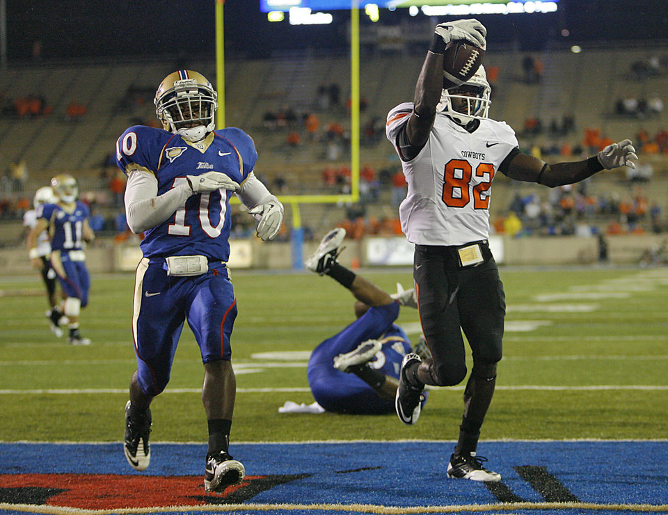 Photo - Oklahoma State's Isaiah Anderson (82) scores a touchdown in front of Tulsa's Justin Skillens (10) during a college football game between the Oklahoma State University Cowboys and the University of Tulsa Golden Hurricane at H.A. Chapman Stadium in Tulsa, Okla., Sunday, Sept. 18, 2011. Photo by Chris Landsberger, The Oklahoman
