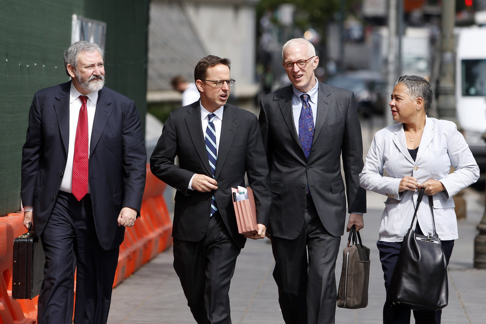 Photo - Lawyers for Argentina including Jonathan Blackman, left, and Carmine Boccuzzi, second left, arrive at federal court for a hearing regarding the country's request to extend deadlines to repay a $1.65 billion debt to U.S. hedge funds, Friday, June 27, 2014, in New York. Judge Thomas P. Griesa has ordered a U.S. bank to return a $539 million payment from Argentina, saying it was illegal to make. The order by the judge came Friday, three days before Argentina faces default if it fails to pay $832 million to the majority of its debt holders. (AP Photo/Jason DeCrow)
