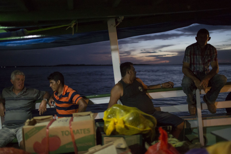"""Photo - In this May 22, 2014, photo, men chat as they travel in the  """"Almirante Barbosa"""" regional boat, on the Solimoes river near Manaus, Brazil. The lumbering wooden vessels are slow going _ the """"Almirante Barbosa"""" chugs at some 20 kilometers (12 miles) an hour, with trips that can stretch out for days or even weeks. (AP Photo/Felipe Dana)"""