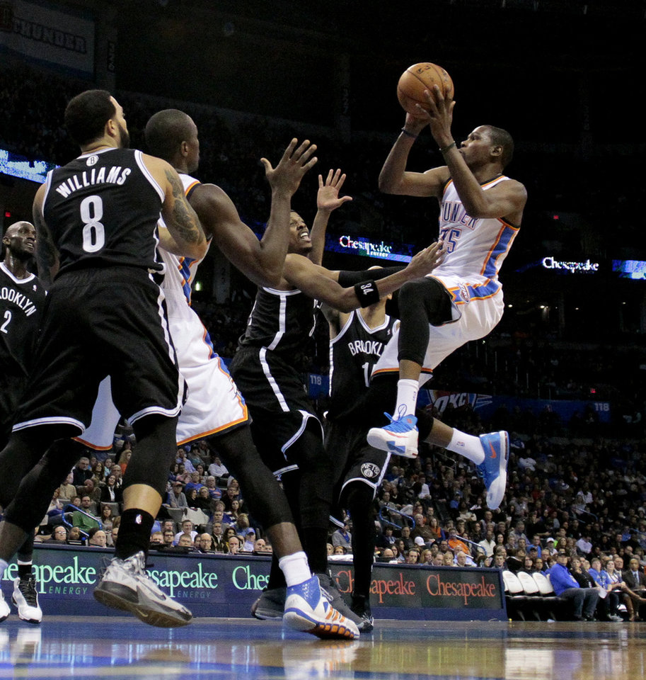 Photo - Thunder's Kevin Durant shoots guarded by Brooklyn's Paul Pierce in the second half of an NBA basketball game where the Oklahoma City Thunder were defeated 95-93 by the Brooklyn Nets at the Chesapeake Energy Arena in Oklahoma City, on Thursday, Jan. 2, 2014. Photo by Steve Sisney, The Oklahoman
