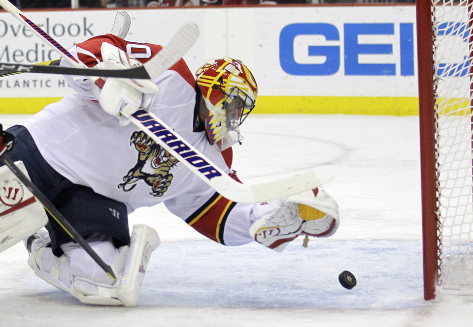 Photo -   Florida Panthers goalie Scott Clemmensen reaches to make a save on a shot by New Jersey Devils' David Clarkson during the second period of Game 6 of a first-round NHL hockey Stanley Cup playoff series, Tuesday, April 24, 2012, in Newark, N.J. (AP Photo/Julio Cortez)