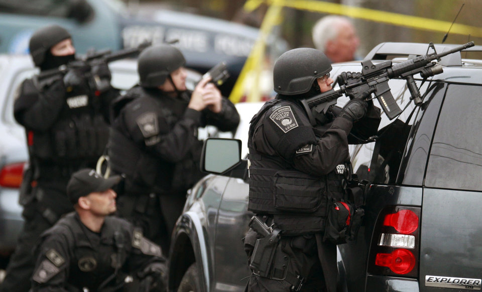 Photo - FILE - In this April 19, 2013 file photo, police in tactical gear surround an apartment building while looking for a suspect in the Boston Marathon bombings in Watertown, Mass. A Harvard University report released Thursday, April 3, 2014, on the response to the bombings was largely positive, but criticized law enforcement for the chaotic gunfight in which one suspect was killed and a police officer seriously injured, because it lacked coordination.  (AP Photo/Charles Krupa, File)