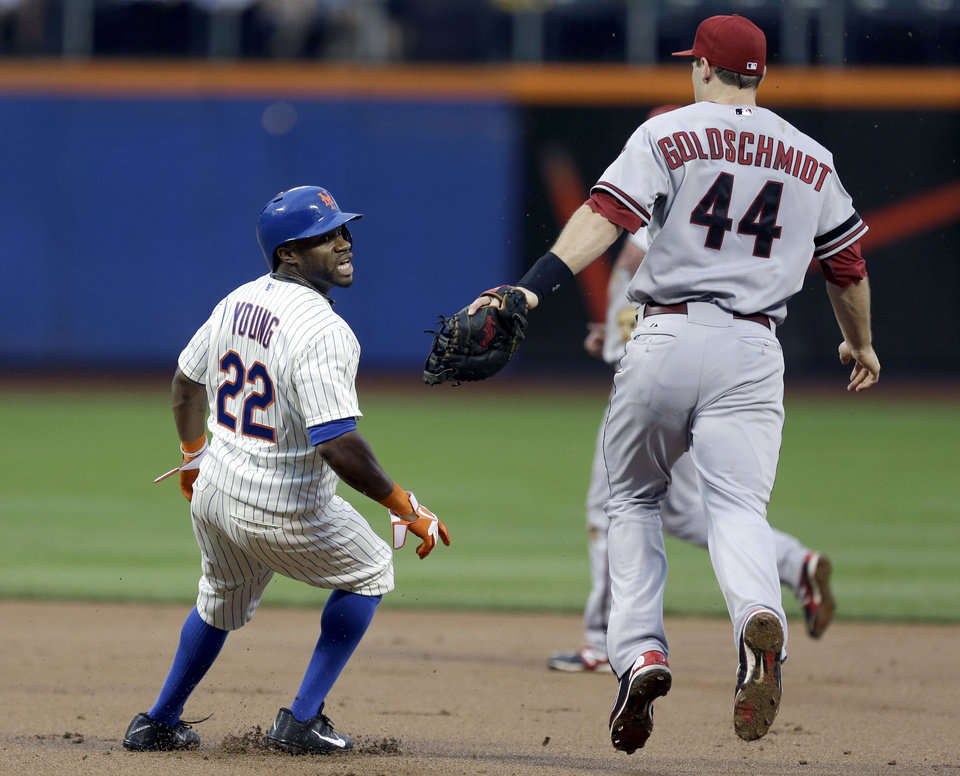 Photo - New York Mets' Eric Young Jr. reacts after being picked off as Arizona Diamondbacks first baseman Paul Goldschmidt gives chase during the first inning of the baseball game at Citi Field, Monday, July 1, 2013, in New York. (AP Photo/Seth Wenig)