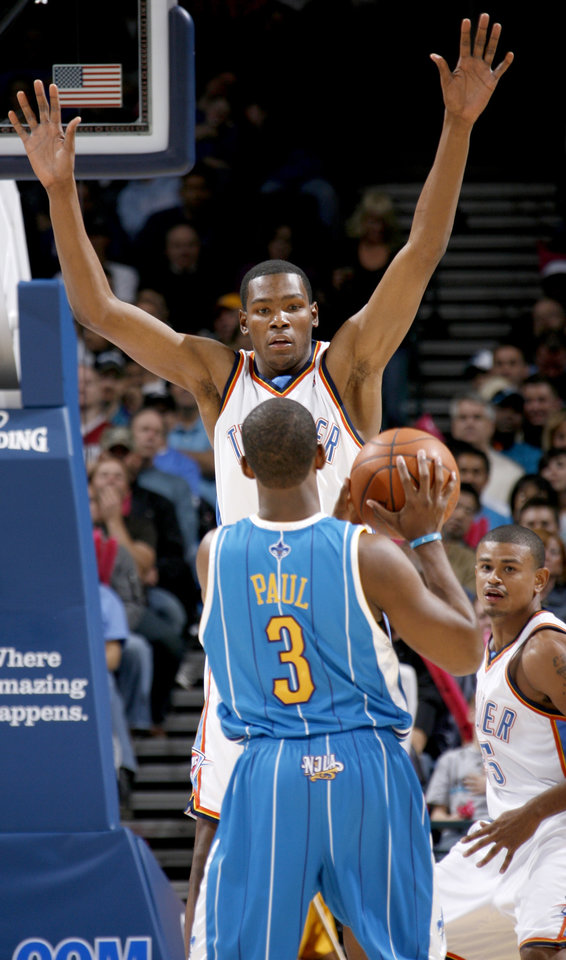 Photo - Oklahoma City's Kevin Durant defends Chris Paul of New Orleans as Earl Watson watches during the NBA basketball game between the Oklahoma City Thunder and the New Orleans Hornets at the Ford Center in Oklahoma City on Friday, Nov. 21, 2008.  BY BRYAN TERRY, THE OKLAHOMAN