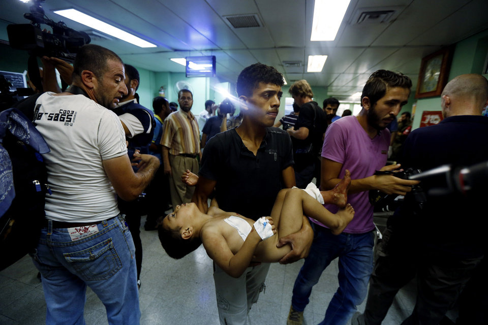 Photo - A Palestinian man carries a child, wounded in an Israeli strike on a compound housing a U.N. school in Beit Hanoun, in the northern Gaza Strip, towards the emergency room of the Kamal Adwan hospital in Beit Lahiya, Thursday, July 24, 2014. Israeli tank shells hit the compound, killing more than a dozen people and wounding dozens more who were seeking shelter from fierce clashes on the streets outside. Gaza health official Ashraf al-Kidra says the dead and injured in the school compound were among hundreds of people seeking shelter from heavy fighting in the area. (AP Photo/Lefteris Pitarakis)