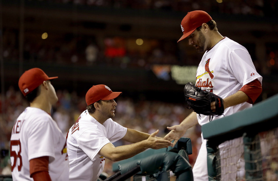 Photo - St. Louis Cardinals starting pitcher Lance Lynn, right, is congratulated by teammates Adam Wainwright, center, and Joe Kelly, left, after being removed from a baseball game against the Pittsburgh Pirates during the seventh inning Wednesday, July 9, 2014, in St. Louis. (AP Photo/Jeff Roberson)