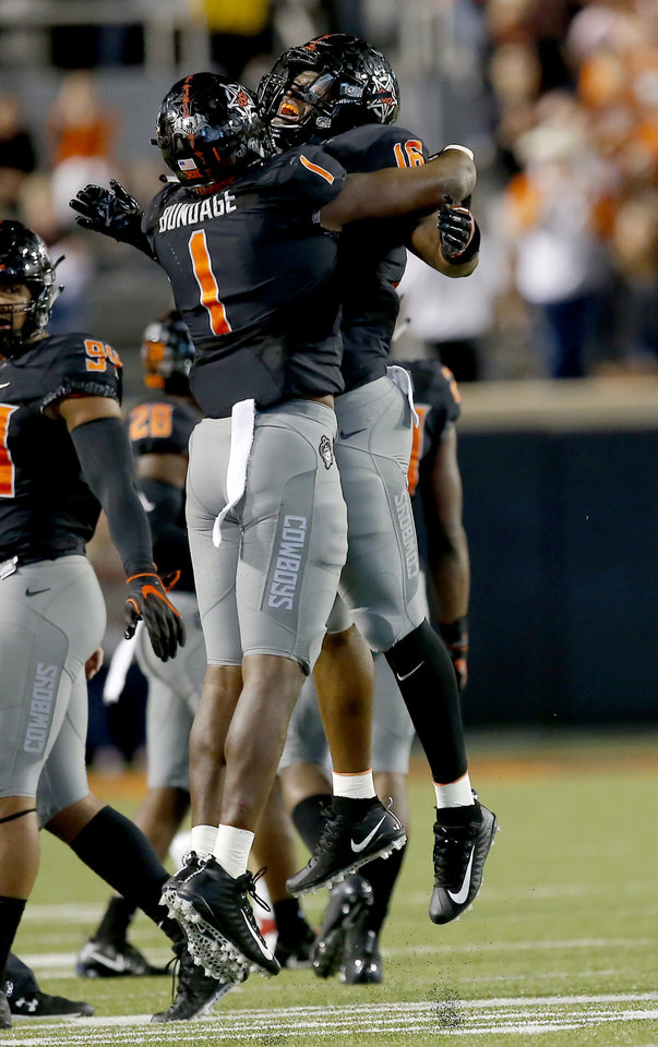 Photo - Oklahoma State's Calvin Bundage (1) and Devin Harper (16) celebrate a play in the third quarter during a college football game between Oklahoma State (OSU) and South Alabama at Boone Pickens Stadium in Stillwater, Okla., Saturday, Sept. 8, 2018. Photo by Sarah Phipps, The Oklahoman