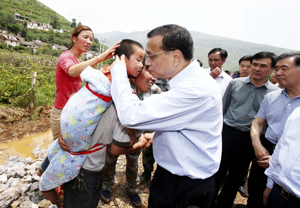 Photo - Chinese Premier Li Keqiang comforts a child at the earthquake zone in the town of Longtoushan in Ludian County in southwest China's Yunnan Province Monday, Aug. 4, 2014. Li walked into the worst-hit Longtoushan   Monday to examined the situation of the earthquake and instructed the quake relief work. (AP Photop/Xinhua, Yao Dawei) NO SALES