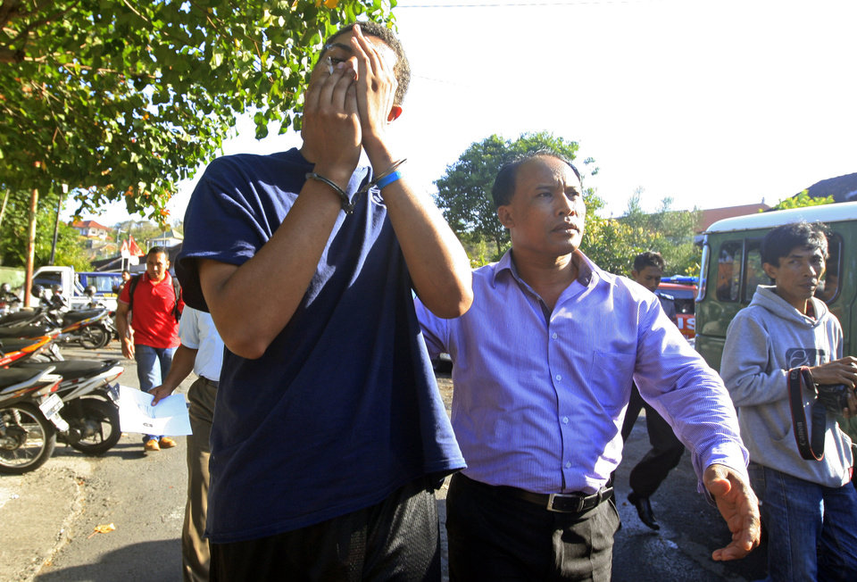 Photo - FILE - In this Wednesday, Aug. 13, 2014 file photo, an Indonesian police officer escorts American Tommy Schaefer, left, as he is brought to the police station for questioning in relation to the death of his girlfriend's mother, in Bali, Indonesia. Schaefer and his girlfriend also American Heather Mack arrested in Indonesia on suspicion of murdering the woman's mother and stuffing her body into a suitcase at a resort hotel are being held under a suicide watch, their appointed lawyer said Wednesday. (AP Photo/Firdia Lisnawati, File)